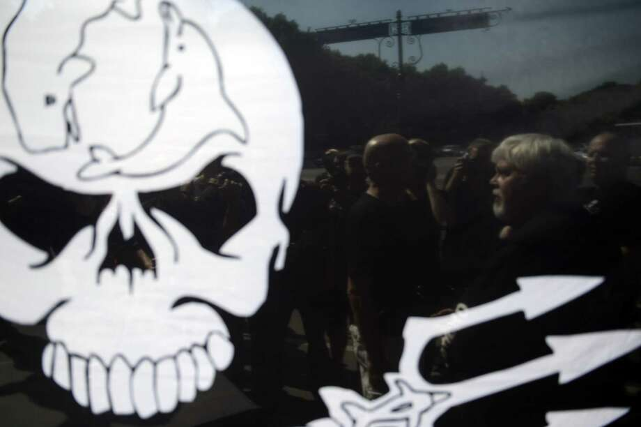 "Paul Watson (R), Canadian founder and president of the Sea Shepherd Conservation Society, can be seen through a flag during a demonstration on May 23, 2012 in Berlin, where the Costa Rican President was expected for a visit. Watson is on bail while German authorities decide whether he can be extradited to Costa Rica on charges stemming from a high-seas confrontation over shark finning in 2002. Watson is accused of ""putting a ship's crew in danger"". The Canadian national is well known for his pursuit and harassment of Japanese whaling boats off Antarctica which in recent years has significantly reduced the number of animals slaughtered. (Photo by ODD ANDERSEN/AFP/GettyImages) Photo: ODD ANDERSEN, Getty Images / 2012 AFP"