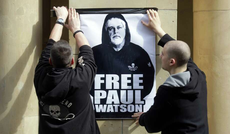 "Activists hang a placard picturing founder of marine conservation group Sea Shepherd, Paul Watson  in front of the Federal Ministry of Justice in Berlin, Germany, on May 18, 2012.  A German court ruled Watson could be freed on bail while authorities decide whether he can be extradited to Costa Rica.He stands accused of ""putting a ship's crew in danger."" (Photo by KAY NIETFELD/AFP/GettyImages) Photo: KAY NIETFELD, Getty Images / 2012 AFP"