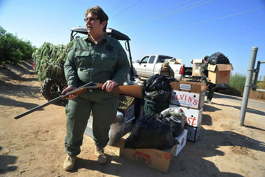 Fresno County Sheriff Margaret Mims shows a shotgun seized in a raid of a 140-acre Fresno County far