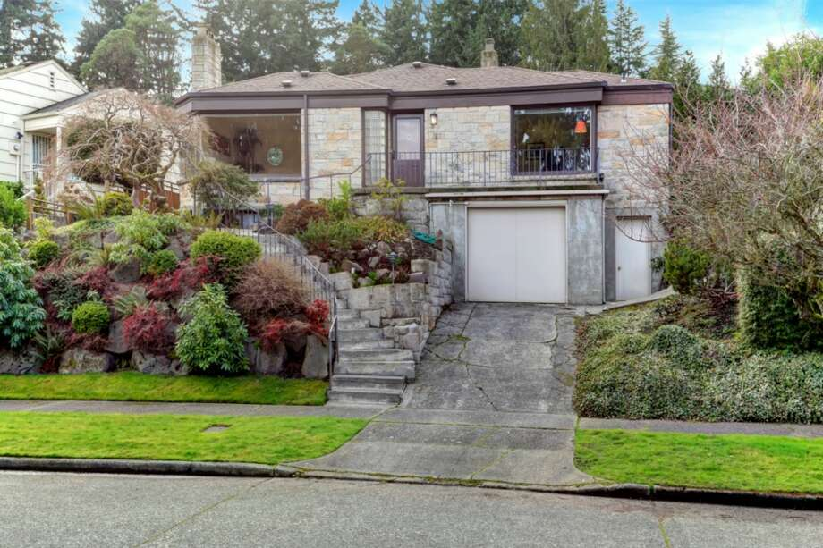 You won't find many nice homes in Seattle's posh Laurelhurst neighborhood for less than $700,000. But here are a few, starting with 5015 Nicklas Place N.E. The 2,710-square-foot house, built in 1941, has three bedrooms, three bathrooms, a wall of windows in the living room, a basement rec room with a fireplace, a front porch, a patio, a tree house, and views of Lake Washington and the Cascade Mountains on a 7,500-square-foot lot. It's listed for $699,000. Photo: Artazum/Courtesy John H. O'Brien/John L. Scott Real Estate