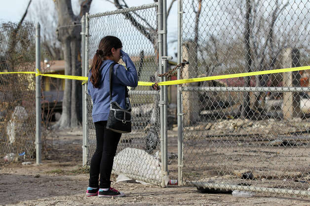 Ten-year-old Mary Ybarra stands in front of what is left of her family's home at the 8100 block of Old Pearsall Road, Tuesday, Feb. 26, 2013. A fire, driven by high wind, tore through the neighborhood and destroyed five home and took the lives of Ybarra's aunt and her two one-year-old cousins. Photo: Jerry Lara, San Antonio Express-News / © 2013 San Antonio Express-News