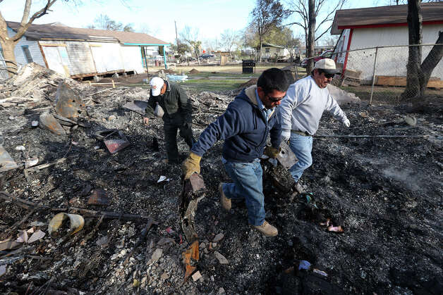 From left, Juan Lugo, Rudy Lugo and Rene Lugo help clean up debris at their brother's three unit apartment building at 8100 block of Old Pearsall Road, Tuesday, Feb. 26, 2013. A multi-structure fire driven by high winds destroyed fives residences in the neighborhood on Monday. Photo: Jerry Lara, San Antonio Express-News / © 2013 San Antonio Express-News