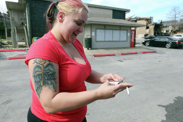 April Steiner, 27, smiles after San Antonio firefighters were able to retreive her purse from her destroyed apartment in the 10800 block of Sahara Street, Tuesday, Feb. 26, 2013. A fire destroyed several units at the complex Monday afternoon. Photo: Jerry Lara, San Antonio Express-News / © 2013 San Antonio Express-News