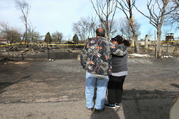 Luis and Rita Fonseca, of Lytle, watch what remains of a multi-structure fire in the 8100 block of Old Pearsall Road, Tuesday, Feb. 26, 2013. In front are the remains of his cousin's house and the scene where a mother and her twin one-year-olds died. The Monday afternoon fire destroyed five houses in the neighborhood. Photo: Jerry Lara, San Antonio Express-News / © 2013 San Antonio Express-News