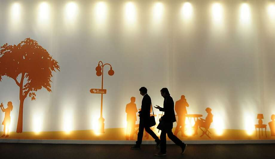 Visitors walk past a mural-sized poster at the Mobile World Congress, the world's largest mobile phone trade show, in Barcelona. Photo: Manu Fernandez, Associated Press