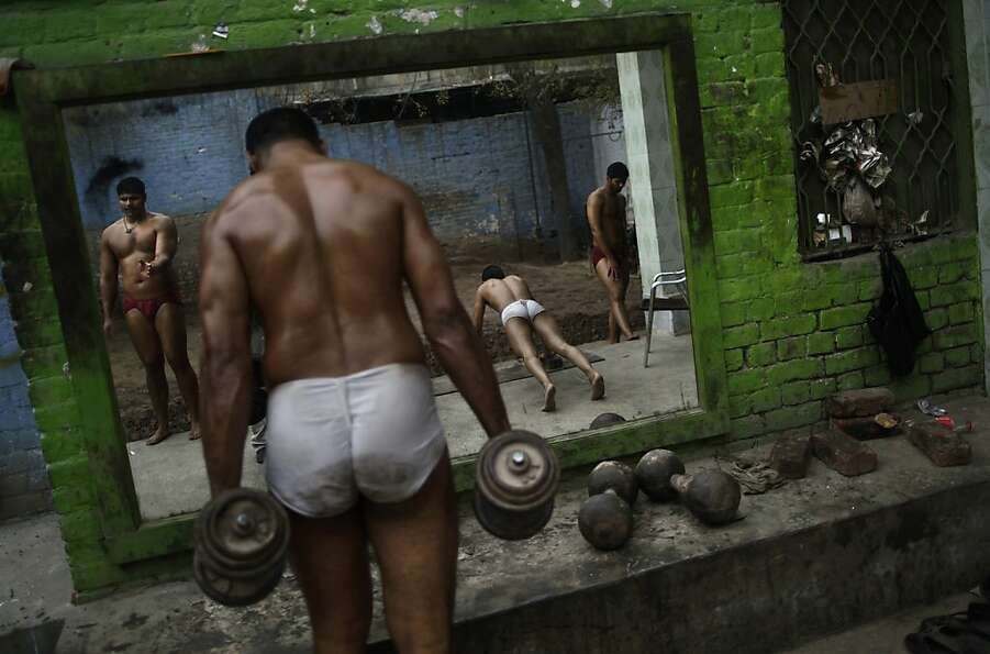 Pakistani Kushti wrestlers warm up before attending their daily training session, at a wrestling clu