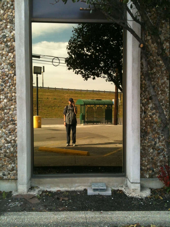Canales took a self-portrait in the reflection of a window at Thad Ziegler Glass.