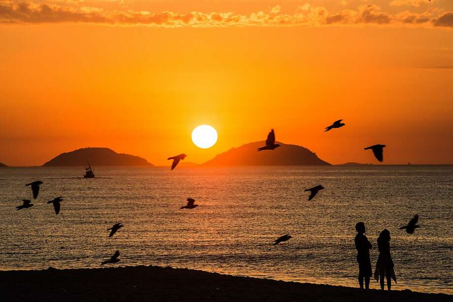 Early birdsshare a romantic moment at sunrise on Rio's Copacabana beach. Photo: Christophe Simon, AFP/Getty Images