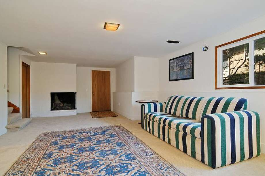 Basement family room of 4402 N.E. 41st St. The 2,260-square-foot house, built in 1959, has four bedrooms, 2.5 bathrooms, a vaulted ceiling with an exposed beam, a wall of windows, a brick fireplace wall, a porch, a deck and a two-car garage on a 4,000-square-foot lot. It's listed for $649,000 Photo: Courtesy Jill Cunningham And Casey Holme/Windermere Real Estate