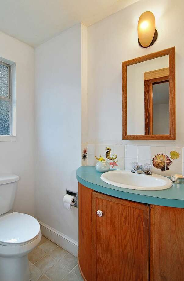 Bathroom of 4402 N.E. 41st St. The 2,260-square-foot house, built in 1959, has four bedrooms, 2.5 bathrooms, a vaulted ceiling with an exposed beam, a wall of windows, a brick fireplace wall, a basement family room with a fireplace, a porch, a deck and a two-car garage on a 4,000-square-foot lot. It's listed for $649,000 Photo: Courtesy Jill Cunningham And Casey Holme/Windermere Real Estate