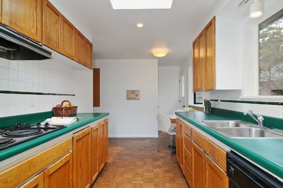 Kitchen of 4402 N.E. 41st St. The 2,260-square-foot house, built in 1959, has four bedrooms, 2.5 bathrooms, a vaulted ceiling with an exposed beam, a wall of windows, a brick fireplace wall, a basement family room with a fireplace, a porch, a deck and a two-car garage on a 4,000-square-foot lot. It's listed for $649,000 Photo: Courtesy Jill Cunningham And Casey Holme/Windermere Real Estate