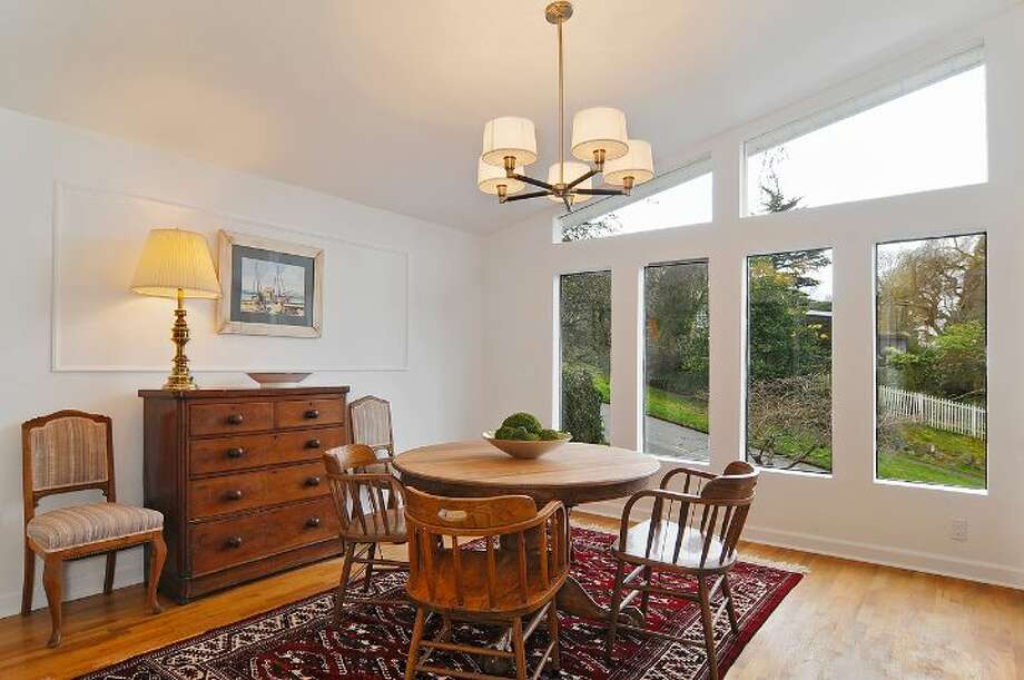Dining room of 4402 N.E. 41st St. The 2,260-square-foot house, built in 1959, has four bedrooms, 2.5 bathrooms, a vaulted ceiling with an exposed beam, a wall of windows, a brick fireplace wall, a basement family room with a fireplace, a porch, a deck and a two-car garage on a 4,000-square-foot lot. It's listed for $649,000 Photo: Courtesy Jill Cunningham And Casey Holme/Windermere Real Estate