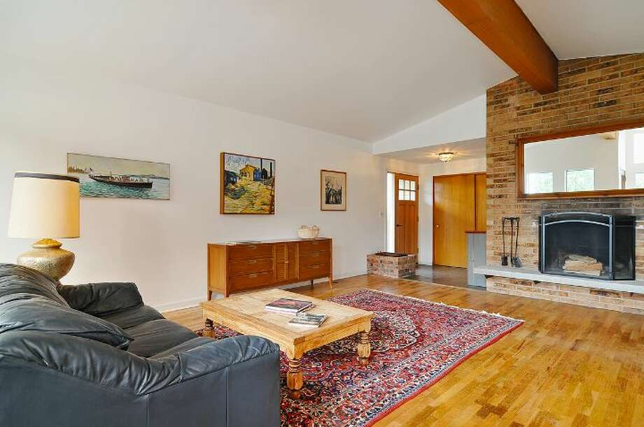 Living room of 4402 N.E. 41st St. The 2,260-square-foot house, built in 1959, has four bedrooms, 2.5 bathrooms, a vaulted ceiling with an exposed beam, a wall of windows, a basement family room with a fireplace, a porch, a deck and a two-car garage on a 4,000-square-foot lot. It's listed for $649,000 Photo: Courtesy Jill Cunningham And Casey Holme/Windermere Real Estate