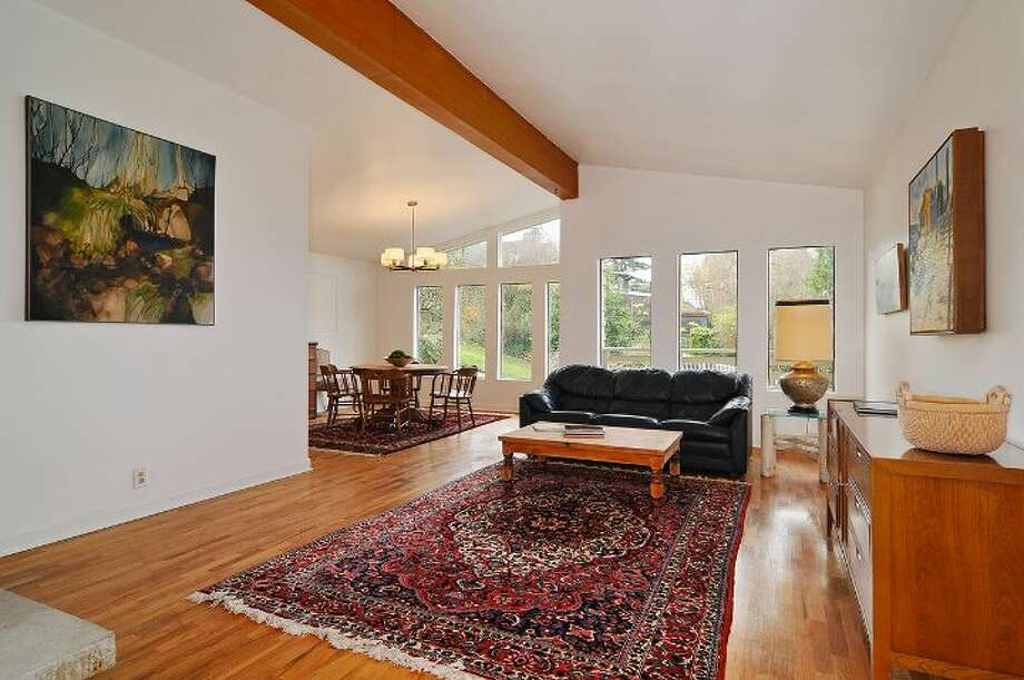 Living room of 4402 N.E. 41st St. The 2,260-square-foot house, built in 1959, has four bedrooms, 2.5 bathrooms, a vaulted ceiling with an exposed beam, a wall of windows, a brick fireplace wall, a basement family room with a fireplace, a porch, a deck and a two-car garage on a 4,000-square-foot lot. It's listed for $649,000 Photo: Courtesy Jill Cunningham And Casey Holme/Windermere Real Estate