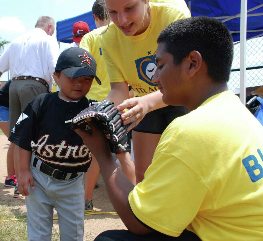 Jordan Garcia, left, checks out a glove with Sydney Adams and Joshua Lopez of the Miracle League at Langham Creek YMCA. Players in the league often have buddies who help the child with disabilities with whatever is necessary to play the game. Photo: Courtesy