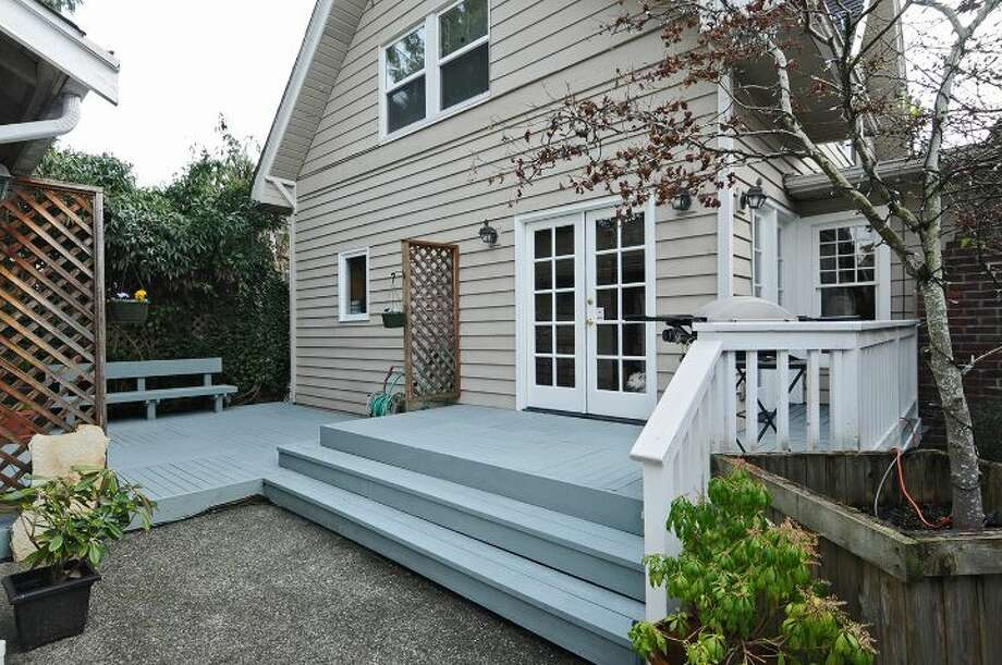 Back patio and deck of 3612 N.E. 43rd St. The 1,880-square-foot Craftsman, built in 1909, has three bedrooms, 1.5 bathrooms, exposed wood moldings and doors, a foyer, walls of windows in the living room, a den, an office nook, a front porch and deck, and a two-car garage on a 5,000-square-foot lot. It's listed for $689,000, although a sale is pending. Photo: Courtesy Kristi Johnson/Windermere Real Estate