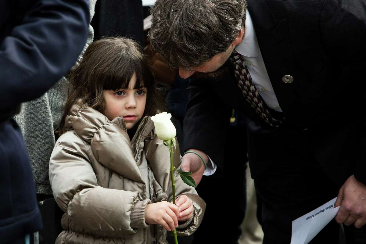 NEW YORK, NY - FEBRUARY 26: Stephen Knapp, a son of a victim from the 1993 World Trade Center bombing, comforts his daughter Alyssa Knapp, age 4, during the 20th Anniversary Ceremony at Ground Zero on February 26, 2013 in New York City. The attack, which utilized a car bomb and hit the north tower, killed six people.
