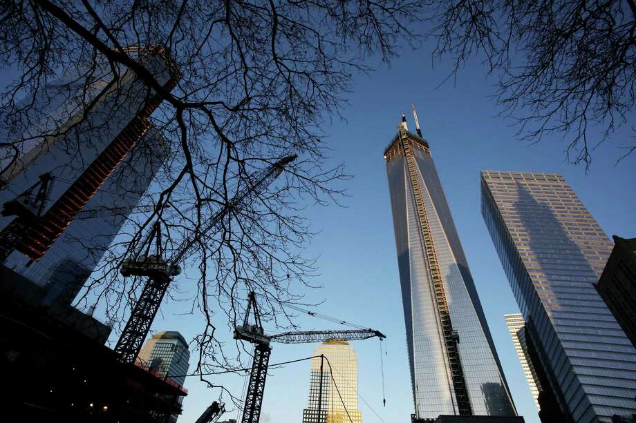 One World Trade Center, right, towers above construction cranes working at the site, Monday, Feb. 25, 2013 in New York. Tuesday will mark the 20th anniversary of the terrorist bombing beneath the World Trade Center that killed six people. Photo: Mark Lennihan, AP / AP