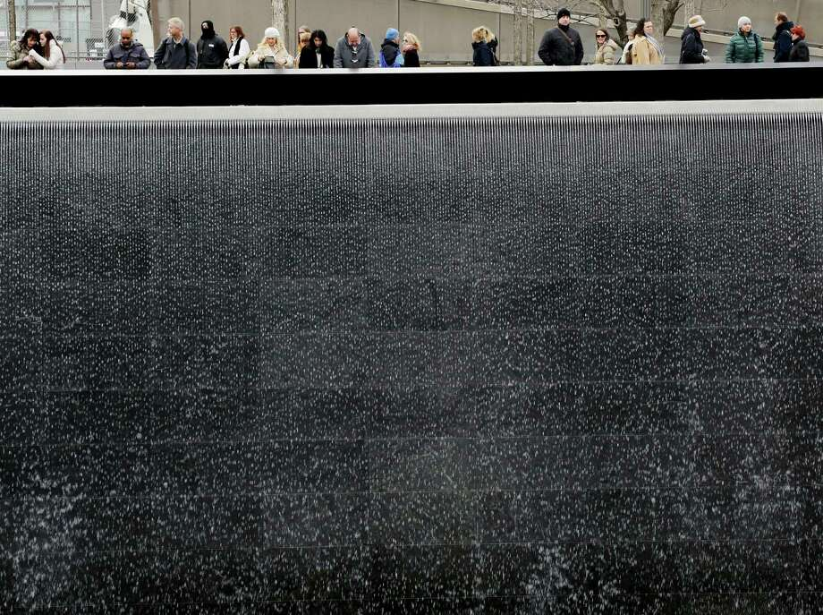 Visitors look over the waterfalls at the National September 11Memorial and Museum, Monday, Feb. 25, 2013 in New York. Tuesday will mark the 20th anniversary of the terrorist bombing beneath the World Trade Center that killed six people in 1993. Photo: Mark Lennihan, AP / AP