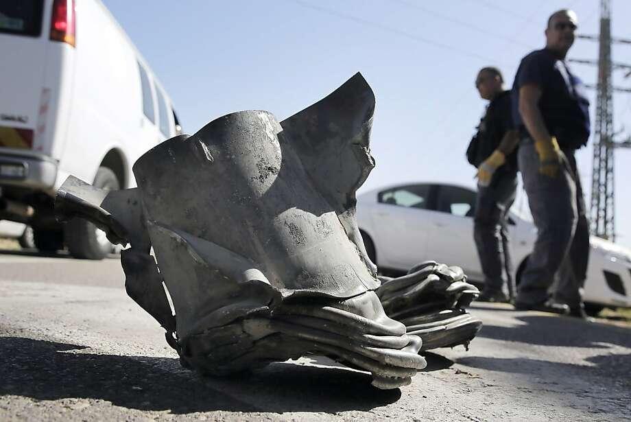 Israeli explosives experts work near where rocket shrapnel sits after an attack near Ashkelon. Photo: Tsafrir Abayov, Associated Press