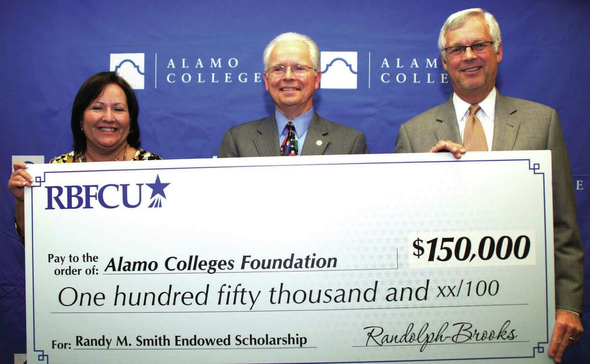 """Dr. Bruce Leslie, Alamo Colleges chancellor, right, accepts a $150,000 """"big check"""" from Randolph-Brooks Federal Credit Union Vice President Anna Postelle to fund a scholarship program in honor of former Randolph-Brooks Federal Credit Union President and CEO Randy M. Smith, center."""