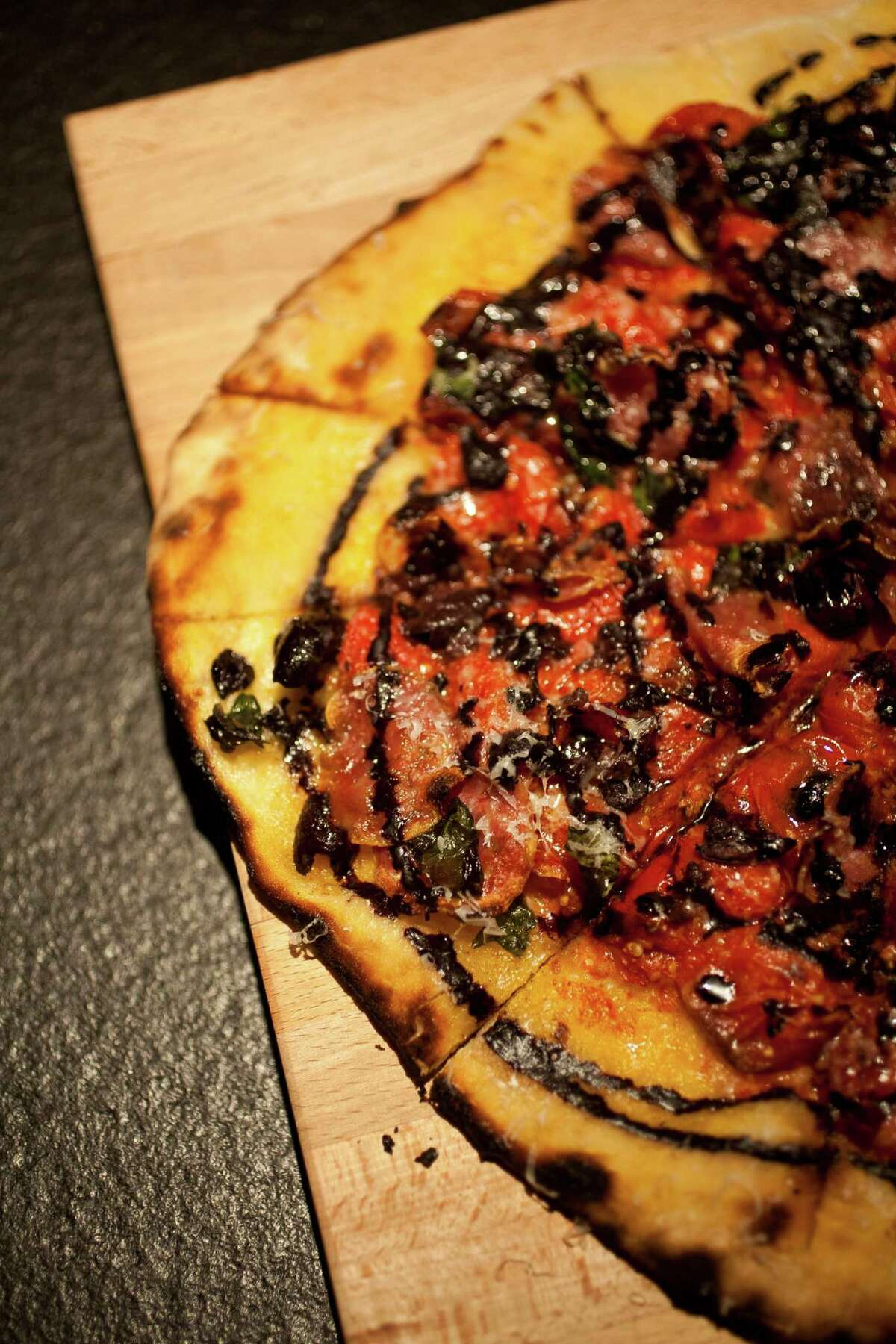 The Pass & Provisions' salumi pizza consists of cured meats with burst tomato, basil and black olive oil.