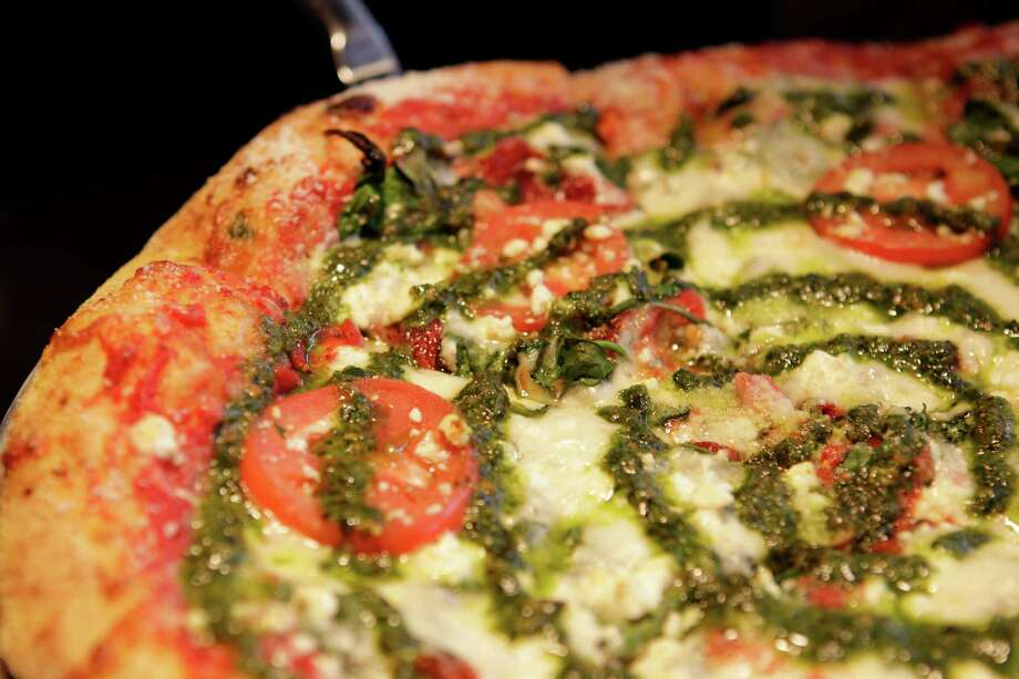 A Kosmic Karma pizza at Mellow Mushroom makes flavorful use of pesto and other fresh ingredients. Photo: Melissa Phillip, Staff / © 2013  Houston Chronicle
