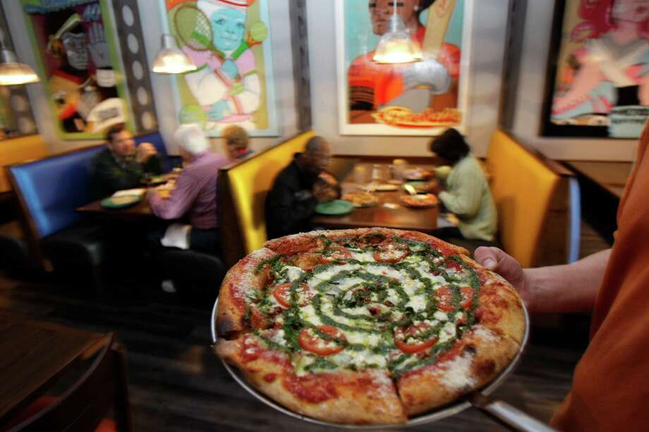 Jesse Cole, general manager, carries a Kosmic Karma pizza at Mellow Mushroom, 16000 Stuebner Airline Rd., Wednesday, Feb. 20, 2013, in Spring. ( Melissa Phillip / Houston Chronicle ) Photo: Melissa Phillip, Staff / © 2013  Houston Chronicle