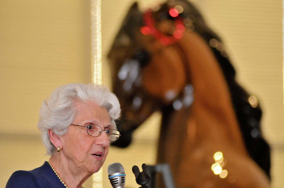 Dorothy Hughes, a Thomas Jefferson High School Lasso alumni from 1941, speaks during a mixer at the school with the current day squad of Lasso's. Behind her is a statue of the school's Mustang mascot. Photo: Robin Jerstad
