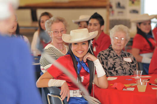 Thomas Jefferson High School Lasso Gabriella Leon smiles while listening to Dorothy Hughes, a Lasso from 1941, speak during a mixer at the school. Behind Leon are the mother-daughter Lasso's of Terry Herrmann, Lasso 1966 (left) and Rena Chambers, Lasso 1944. Photo: Robin Jerstad