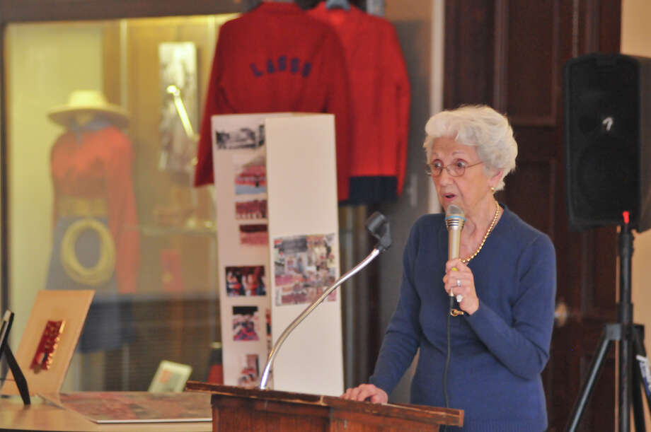 Dorothy Hughes, a Thomas Jefferson High School Lasso alumni from 1941, speaks during a mixer at the school with the current day squad of Lasso's. Behind her is an exhibit of historical Lasso uniforms. Photo: Robin Jerstad