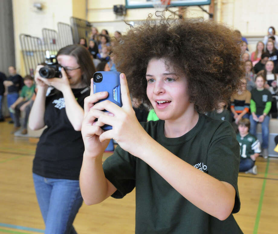 Eastern Middle School eighth-grader Jimmy Catalano, 13, takes a photo of the teachers team at the start of the student/faculty basketball game to raise money for the Sandy Hook Elementary School physical education department held in the gym at the school in Riverside, Tuesday afternoon, Feb. 26, 2013. According to Craig Knop, a physical education teacher at the school, who lives in Newtown, the organziers of the event hoped to raise $4,000. The teachers won the game 29-28. Photo: Bob Luckey / Greenwich Time