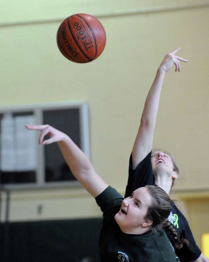 At left, Eastern Middle School eighth-grader Emily Anderson, 13, jumps center against teacher Devon Kelly during the student/faculty basketball game to raise money for the Sandy Hook Elementary School physical education department held in the gym at the school in Riverside, Tuesday afternoon, Feb. 26, 2013. According to Craig Knop, a physical education teacher at the school, who lives in Newtown, the organziers of the event hoped to raise $4,000. The teachers won the game 29-28. Photo: Bob Luckey / Greenwich Time