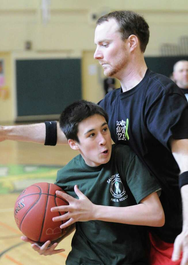 Patrick McTiernan, 13, an eighth-grader at Eastern Middle School, tries to get past teacher Greg Kelly during the student/faculty basketball game to raise money for the Sandy Hook Elementary School physical education department that was held in the gym at the school in Riverside, Tuesday afternoon, Feb. 26, 2013. According to Craig Knop, a physical education teacher at the school who lives in Newtown, the organziers of the event hoped to raise $4,000. The teachers won the game 29-28. Photo: Bob Luckey / Greenwich Time