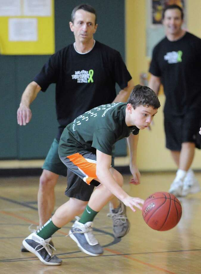 Harry Spiegel, 14, an eighth-grader at Eastern Middle School, gets past teacher Bruce Johnson during the student/faculty basketball game to raise money for the Sandy Hook Elementary School physical education department that was held in the gym at the school in Riverside, Tuesday afternoon, Feb. 26, 2013. According to Craig Knop, a physical education teacher at the school who lives in Newtown, the organziers of the event hoped to raise $4,000. The teachers won the game 29-28. Photo: Bob Luckey / Greenwich Time