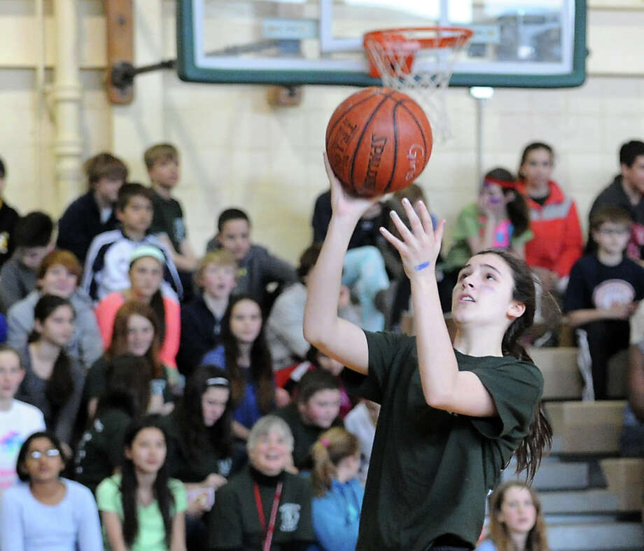 Shaye Galletta, 13, an eighth-grader at Eastern Middle School, scores a basket during the student/faculty basketball game to raise money for the Sandy Hook Elementary School physical education department that was held in the gym at the school in Riverside, Tuesday afternoon, Feb. 26, 2013. According to Craig Knop, a physical education teacher at the school who lives in Newtown, the organziers of the event hoped to raise $4,000. The teachers won the game 29-28. Photo: Bob Luckey / Greenwich Time
