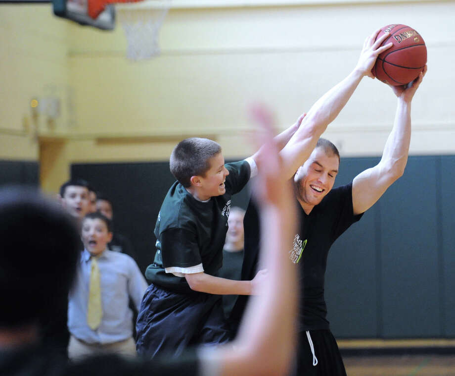 Shawn Cavanaugh, an Eastern Middle School physical education teacher, holds the ball high to keep it away from eighth-grade student Jackson Trimmer in the closing seconds of the student/faculty basketball game held in the gym at the school in Riverside, Tuesday afternoon, Feb. 26, 2013. According to Craig Knop, a physical education teacher at the school who lives in Newtown, the event was a fund-raiser for the Sandy Hook Elementary School physical education department and organizers from the Eastern Middle School physical education department were hoping to raise $4,000. The teachers won the game 29-28. Photo: Bob Luckey / Greenwich Time