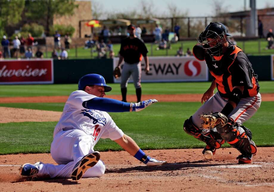 Los Angeles Dodgers' Tim Federowicz, left, scores on a double by Skip Schumaker as San Francisco Giants catcher Guillermo Quiroz, right, bobbles the throw during the second inning of an exhibition spring training baseball game on Tuesday, Feb. 26, 2013 in Glendale. Ariz. (AP Photo/Marcio Jose Sanchez) Photo: Marcio Jose Sanchez, Associated Press / AP