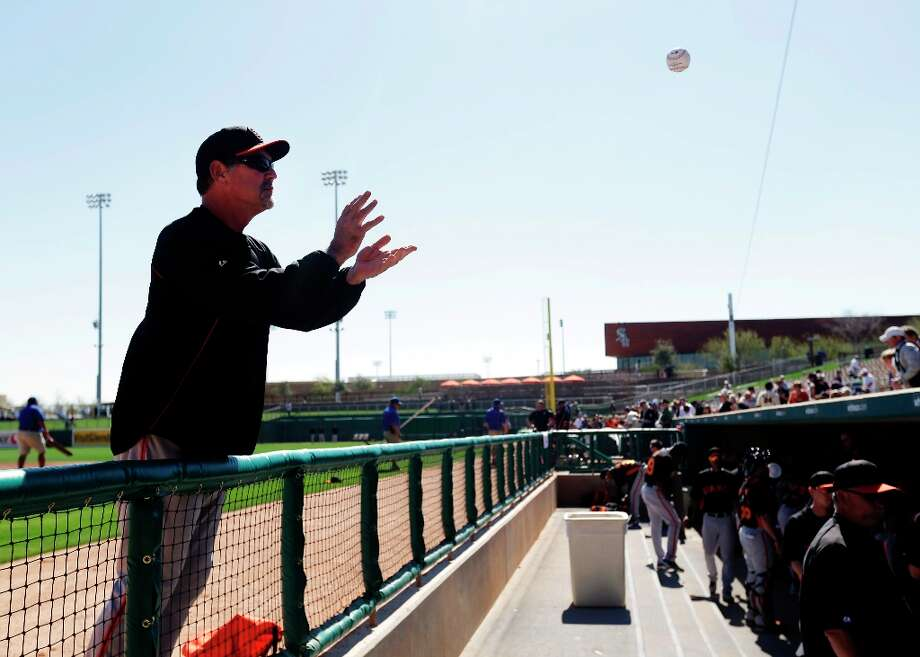 San Francisco Giants manager Bruce Bochy catches a ball from a fan to signs autographs before an exhibition spring training baseball game against the Los Angeles Dodgers on Tuesday, Feb. 26, 2013 in Glendale. Ariz. (AP Photo/Marcio Jose Sanchez) Photo: Marcio Jose Sanchez, Associated Press / AP