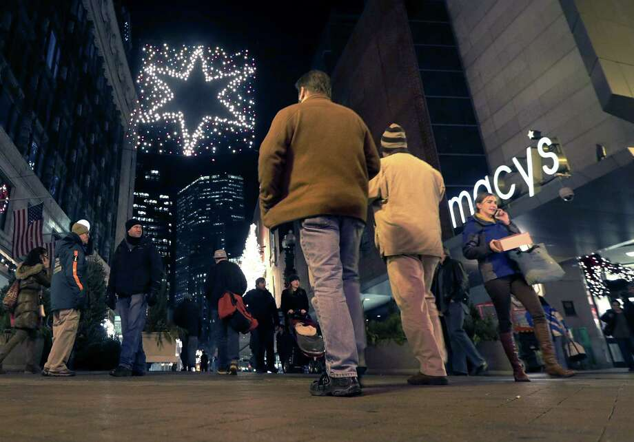 In this Thursday, Dec. 13, 2012 photo, shoppers walk past a Macy's at the Downtown Crossing in Boston. Macy's reported Tuesday, Feb. 26, 2013, a fourth-quarter profit that beat Wall Street expectations as its strategy of tailoring merchandise to local markets paid off during the holiday season.  (AP Photo/Charles Krupa) Photo: Charles Krupa