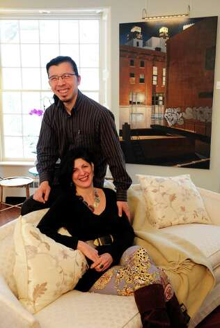 "Jeanine Esposito and husband Frederic Chiu sit in front an oil painting by Duvian Montoya, ""A New York Light,"" at their Westport home Tuesday, Feb. 26, 2013.  The couple hosts art events in their home called Arts Immersion Salons, through their non-profit organization, Beechwood Arts. Photo: Autumn Driscoll / Connecticut Post"