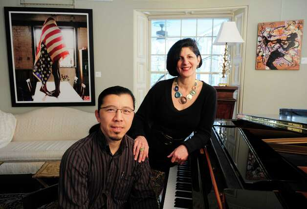 "Jeanine Esposito and husband Frederic Chiu sit between two works of art, ""Flag,""a photograph by Chris Craymer, left, and an enamel painting"" Sketches of Miles"" by Jamane West, at their Westport home Tuesday, Feb. 26, 2013.  The couple hosts art events in their home called Arts Immersion Salons through their non-profit organization, Beechwood Arts. Photo: Autumn Driscoll / Connecticut Post"