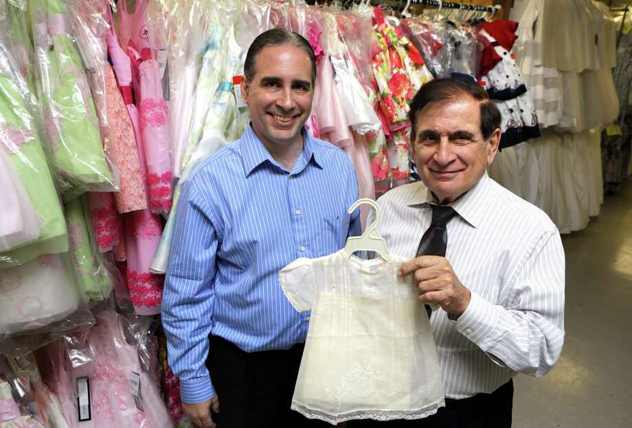 Charles I Castro III, left, and his father Charles I Castro Jr., hold an original dress their company made in the 40's, in their new location just off Austin Highway. C.I. Castro and Co.  has been in business for 91 years, Friday, Feb. 22, 2013. Photo: Bob Owen, San Antonio Express-News / © 2012 San Antonio Express-News