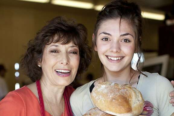 Lenore Colarusso-Denoix, co-owner of Casse Croute french bakery, with employee Nina Kassardjian, 19, holding loaves, at the bakery in Livermore, Calif., Sunday, February 24, 2013.