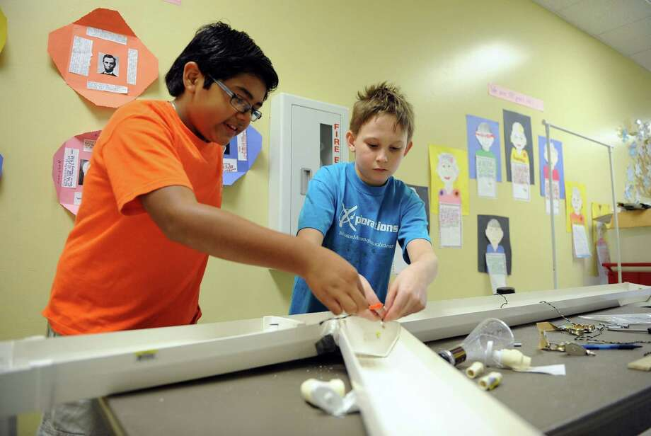 Fourth graders Alfredo Vazquez, left, and Robert Blair erecting a water system to deliver mail for the Odyssey of the Mind competition at Walnut Bend Elementary. Photo: Thomas Nguyen, Freelance / Freelance
