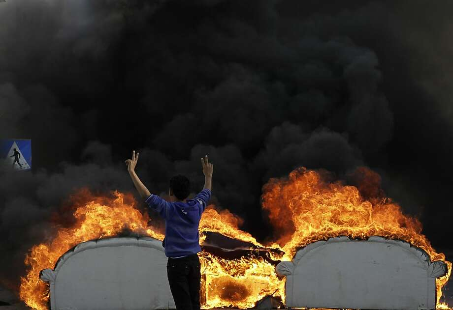Down with matching sofas!An anti-government protester flashes the victory sign as a furniture set burns in a street in Malkiya, Bahrain. Photo: Hasan Jamali, Associated Press