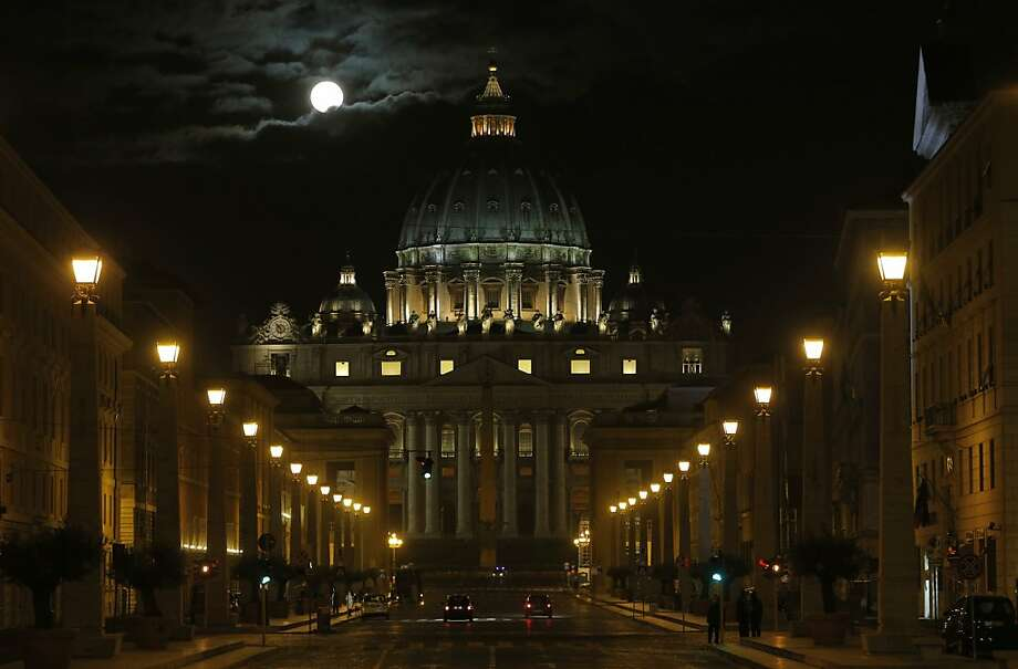 The full moon is seen above the St. Peter's Basilica at the Vatican, early Tuesday, Feb. 26, 2013. Pope Benedict XVI has changed the rules of the conclave that will elect his successor, allowing cardinals to move up the start date if all of them arrive in Rome before the usual 15-day transition between pontificates. Benedict signed a legal document, issued Monday, with some line-by-line changes to the 1996 Vatican law governing the election of a new pope. It is one of his last acts as pope before resigning Thursday. (AP Photo/Dmitry Lovetsky) Photo: Dmitry Lovetsky, Associated Press