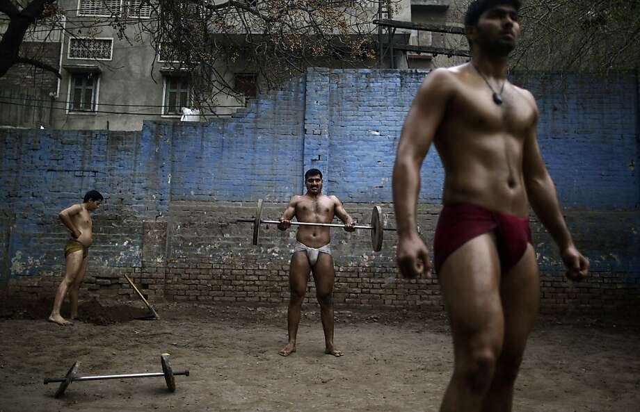 Pakistani Kushti wrestlers warm up in the ring before fighting as part of their daily training, at a wrestling club in Lahore, Pakistan, Tuesday, Feb. 26, 2013. Kushti, an Indo-Pakistani form of wrestling, is several thousand years old and is a national sport in Pakistan. (AP Photo/Muhammed Muheisen) Photo: Muhammed Muheisen, Associated Press