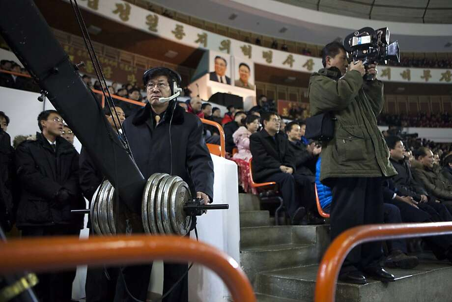North Korean cameramen use an elevated boom camera, left, and a older film camera, right, to cover the opening ceremony of a figure skating exhibition event at an ice skating rink in Pyongyang, North Korea on Friday, Feb. 15, 2013. (AP Photo/David Guttenfelder) Photo: David Guttenfelder, Associated Press