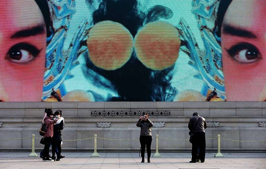 Chinese visitors take souvenir photos in front of a giant video screen showing cultural images at Tiananmen Square in Beijing Tuesday, Feb. 26, 2013. (AP Photo/Andy Wong) Photo: Andy Wong, Associated Press